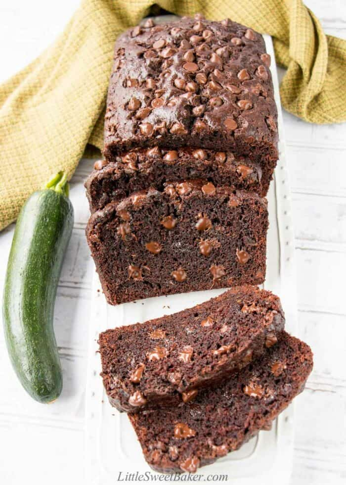 A loaf of double chocolate zucchini bread on a white platter with a few slices cut.