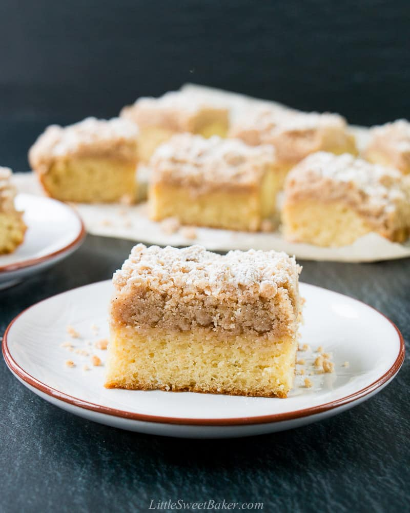 A slice of crumb cake on a plate with the rest of the cake slices in the background.