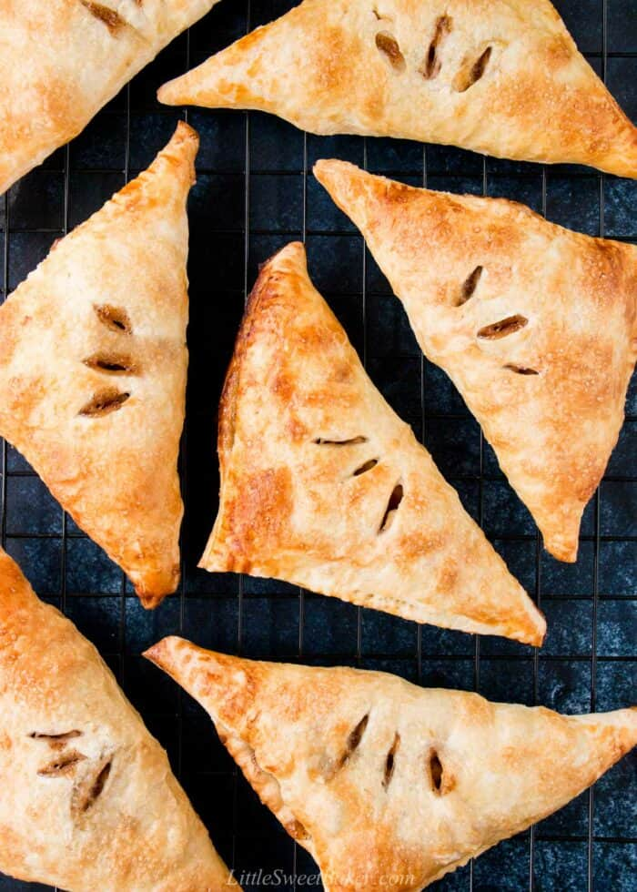 Puff pastry apple turnovers on a cooling rack.