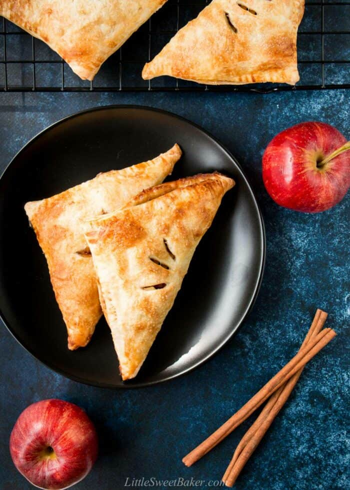 Puff pastry apple turnovers on a black plate with apple and cinnamon stick around.