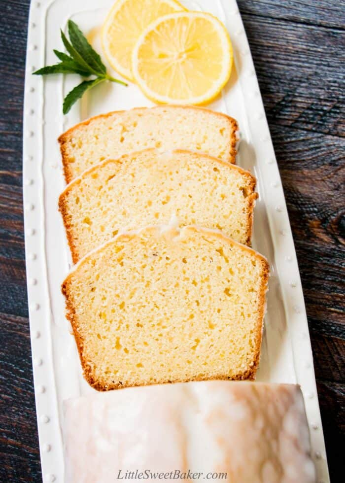 Three slices of lemon pound cake on a white serving plate with some lemon slices and mint twig.
