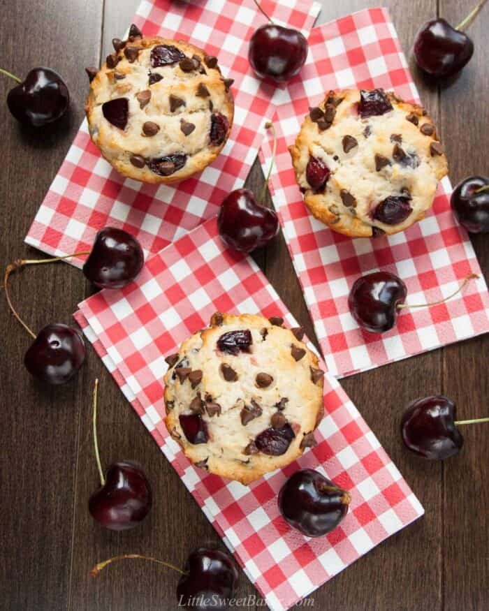 An overhead view of cherry chocolate chip muffins on red plaid napkins and surrounded by black cherries.