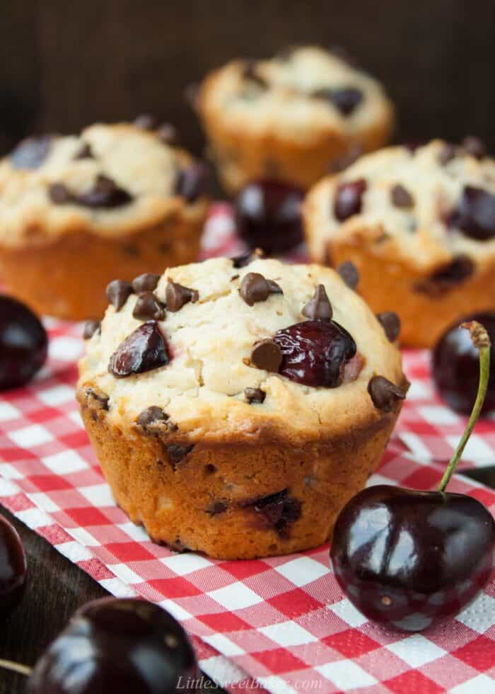 Cherry chocolate chip muffins on red plaid napkins.
