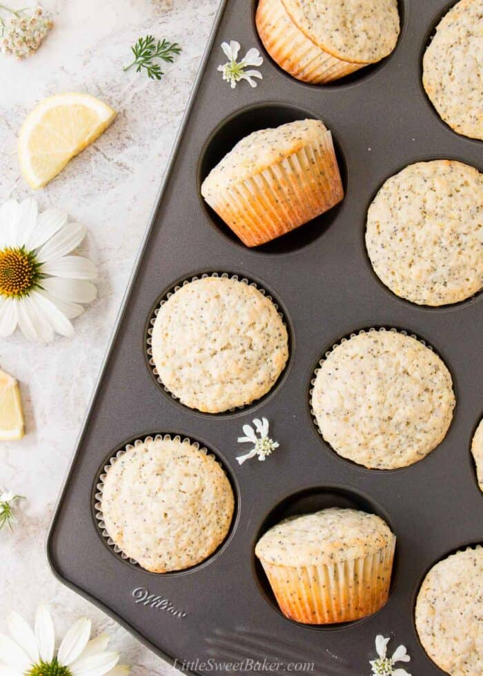 A pan of lemon poppy seed muffins on a marble surface with flowers.