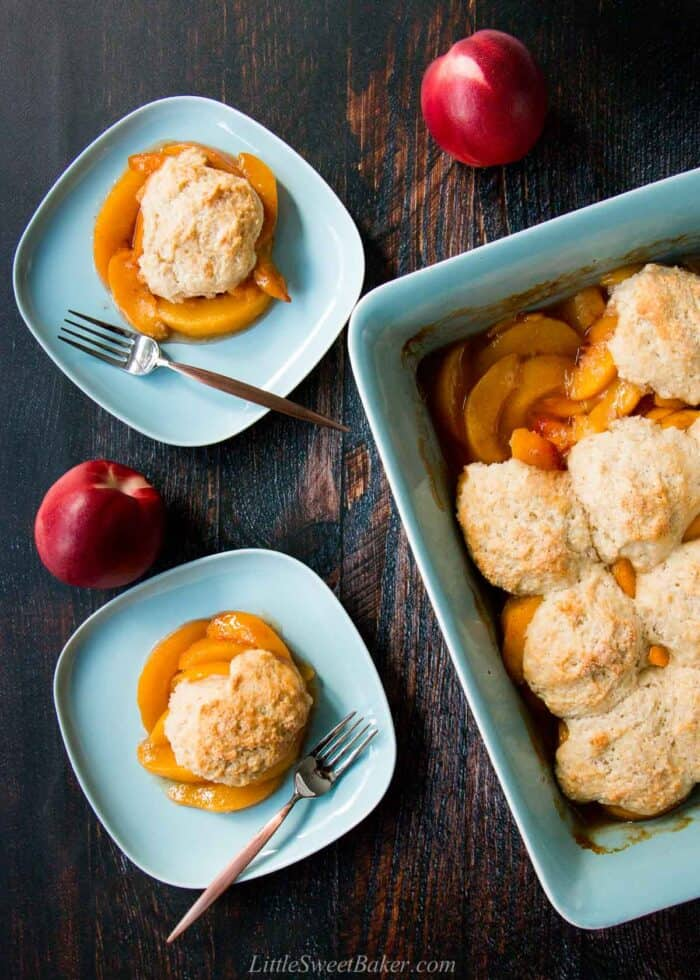 Homemade peach cobbler in a tray and two serving plates on a wooden table surrounded by two peaches.