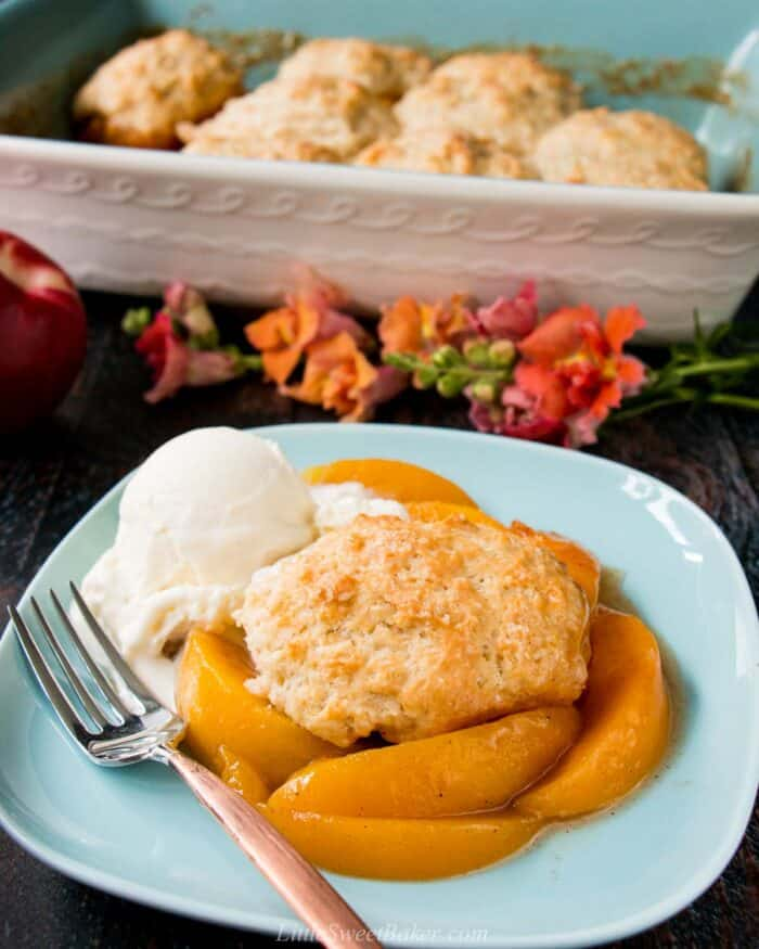 Peach cobbler with biscuits on a blue plate with ice cream.