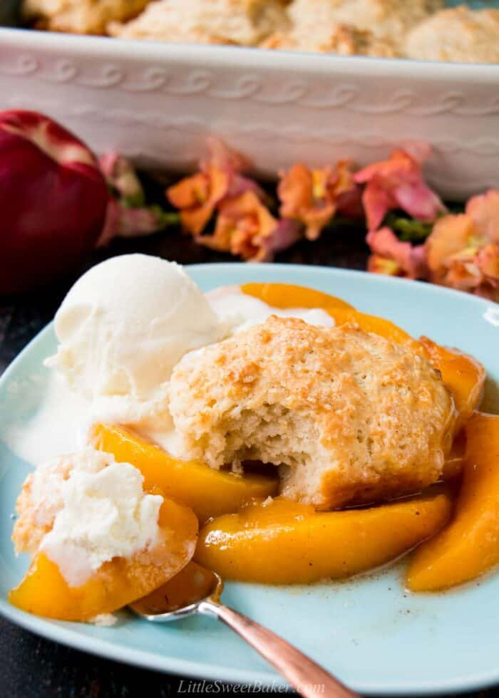 Peach cobbler served with ice cream on a light blue plate.
