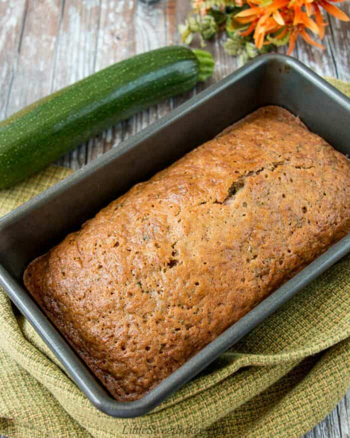 A zucchini loaf in a baking pan with a green dish towel and fresh zucchini beside it.