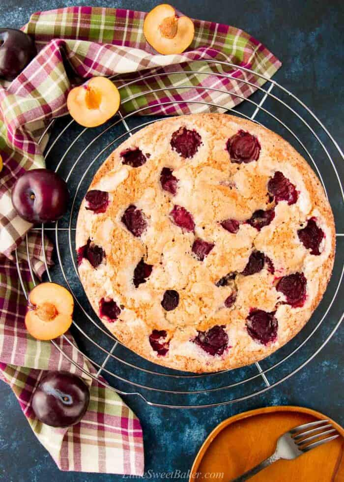 A fresh plum cake on a wire rack with a plaid dish towel and plums around it.