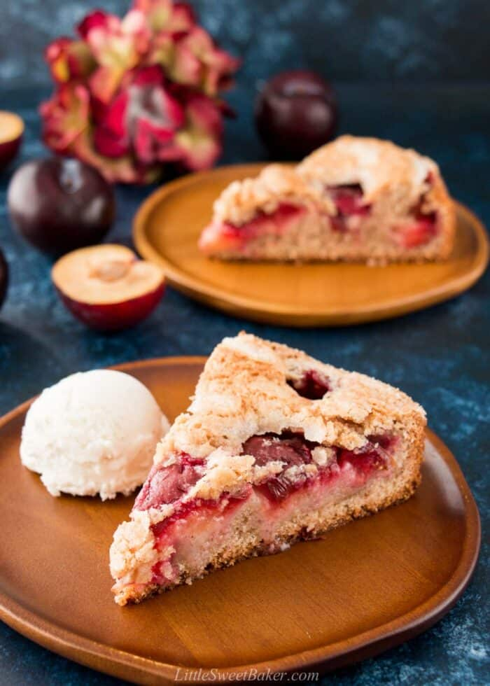 A slice of plum cake on a wooden plate with a scoop of ice cream.