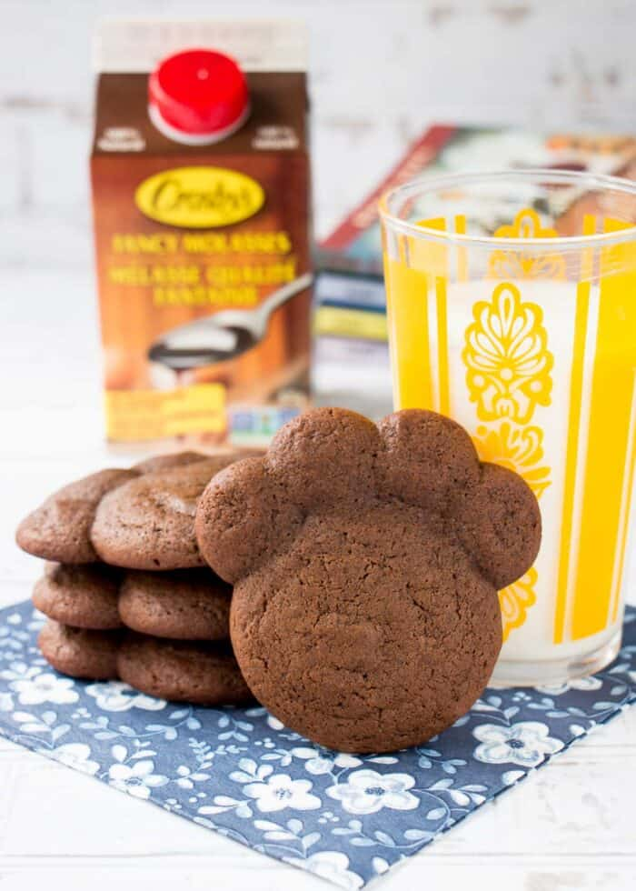 chocolate molasses bear paw cookies on a blue floral napkin with a glass of milk