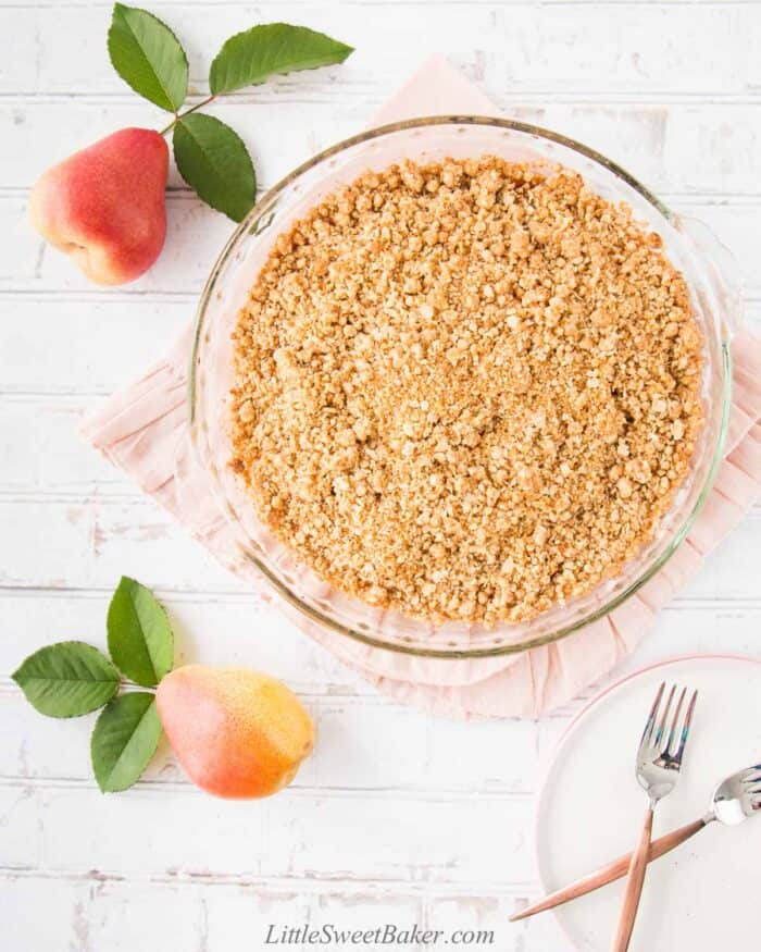 A whole plate of easy pear crisp on a pink napkin with two pears around it.