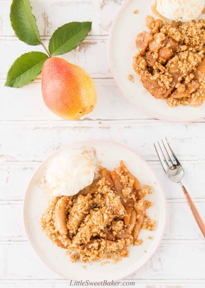 Two plates of pear crisp with ice cream.
