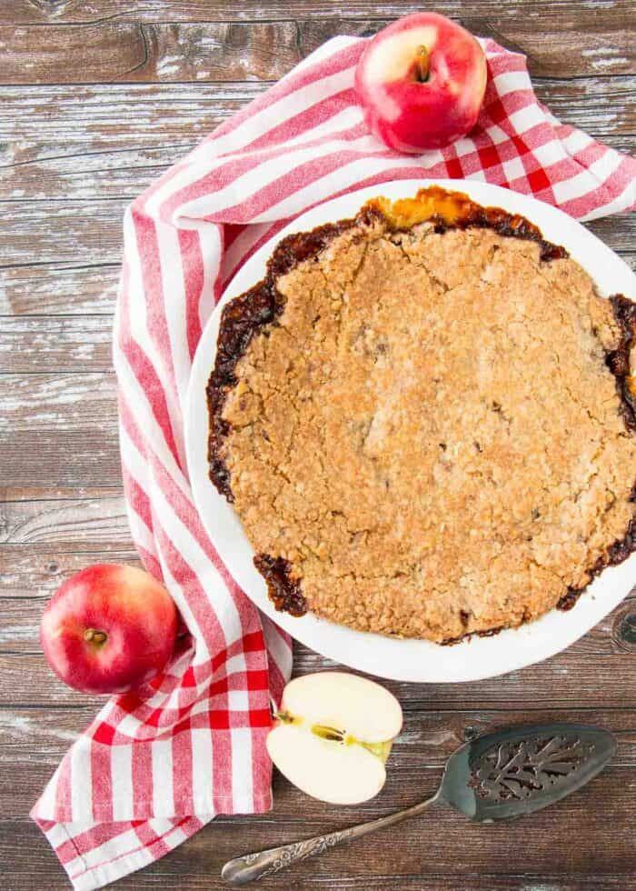 A whole Swedish apple oatmeal pie on a wooden table with a red striped dish clothe and apples around it.