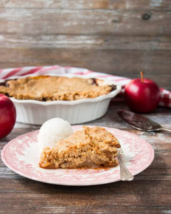 A slice of Swedish apple pie with a scoop of ice cream in a vintage plate.