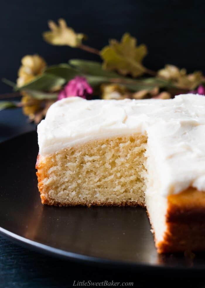 A vanilla snack cake on a black plate.