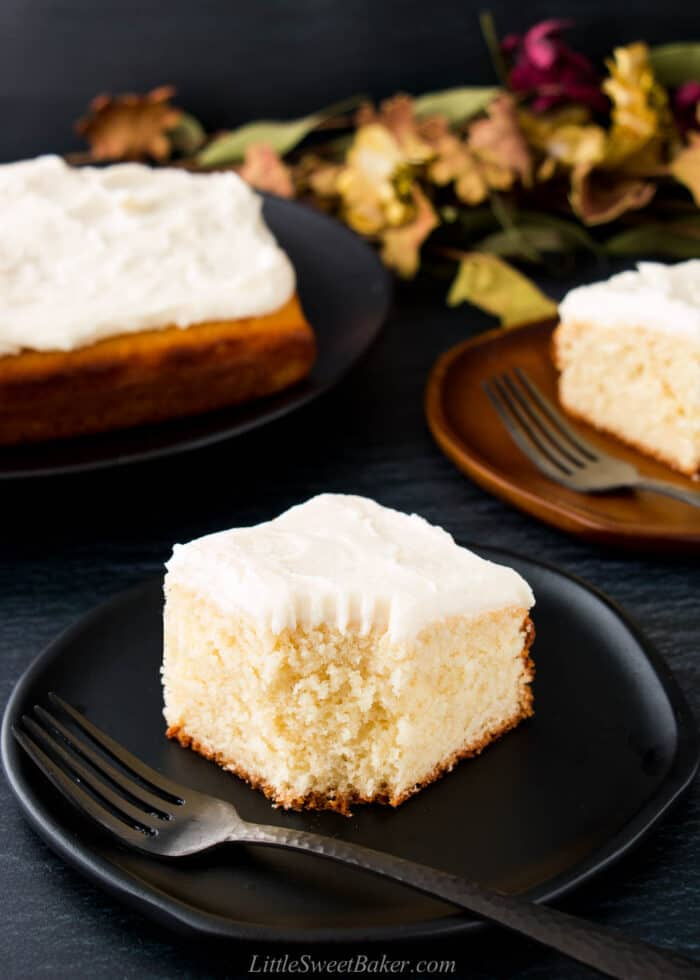 A slice of vanilla butter cake on a black plate with a piece missing.