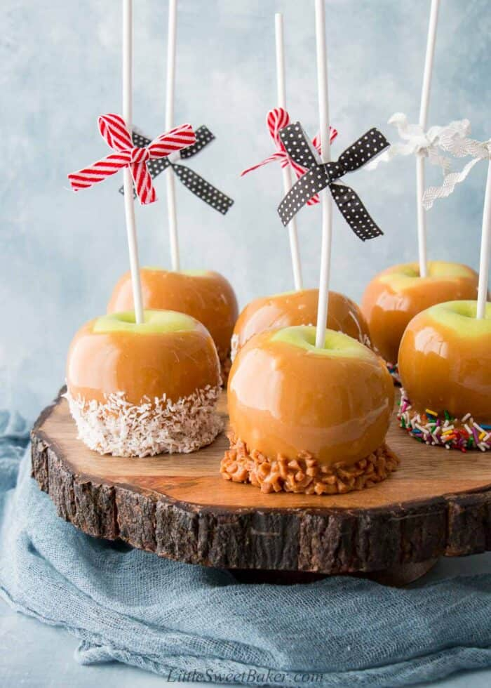 Six caramel apples on a live edge wooden board.