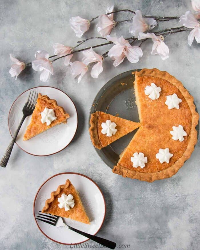 A chess pie in a pie pan with two slices plated and light pink flowers on a light gray background.