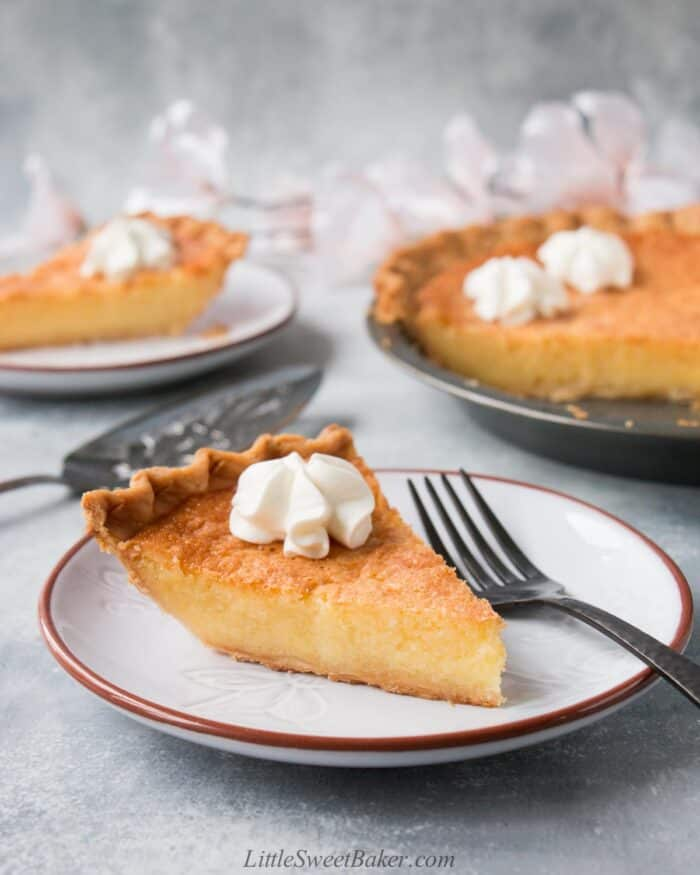 A slice of chess pie with whipped cream on a light gray plate.