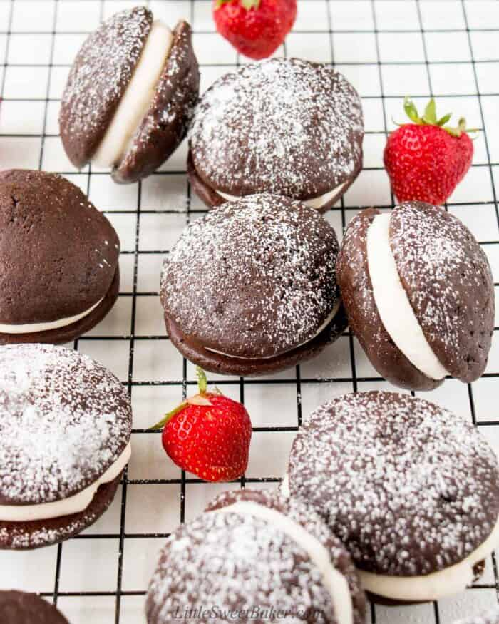 A bunch of whoopie pies on a cooling rack dusted with powdered sugar.