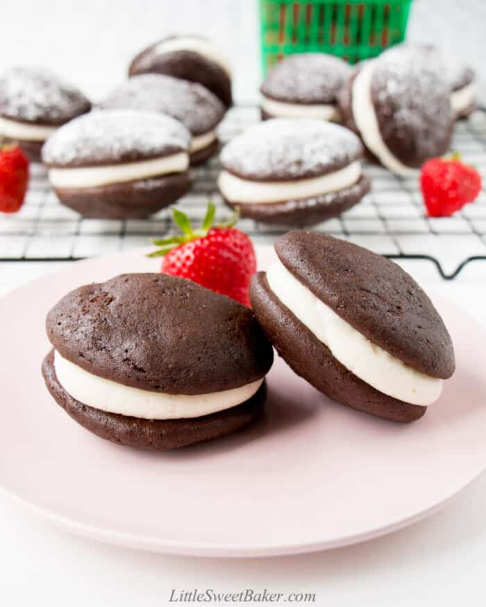 Two chocolate whoopie pies on a pink plate.