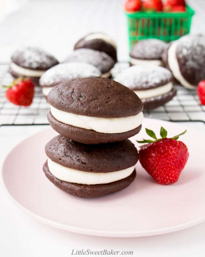 Two whoopie pies stacked on a pink plate with a strawberry.