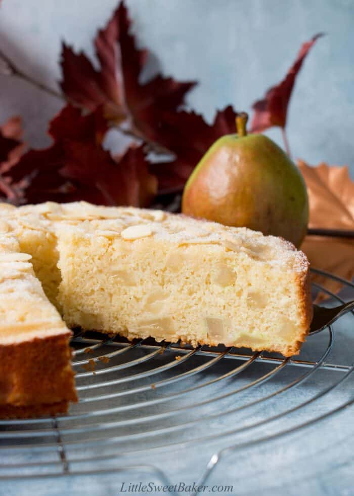 A slice of pear cake getting removed from the whole cake on a cooling rack.