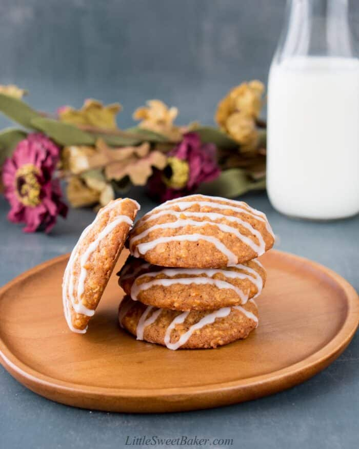 Four pumpkin oatmeal cookies on a wooden plate with a glass of milk and flowers behind.
