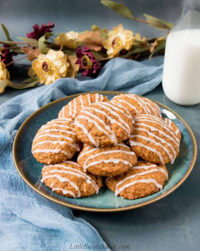 A plate of pumpkin oatmeal cookies with a glass of milk, blue silk cloth and flowers.