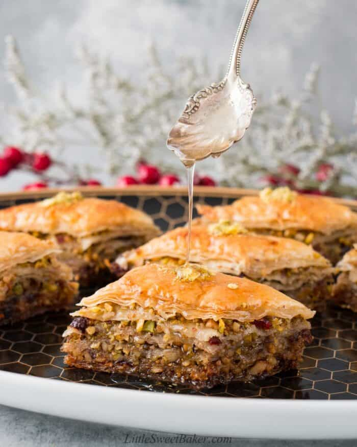 A plate of baklava made with pistachios and cranberries being drizzled with honey syrup.