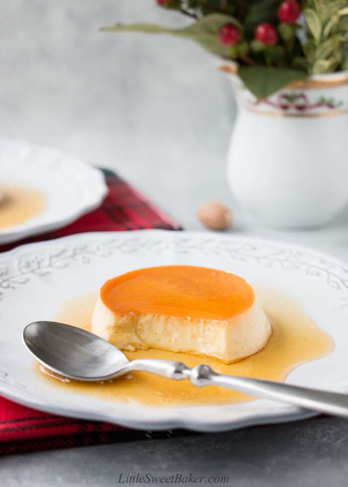 eggnog creme caramel on a light gray plate with spoon.