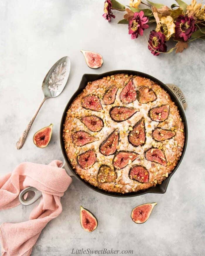 Fig cake in a skillet with some fresh figs around, pink cloth on handle and on a light gray backgorund.