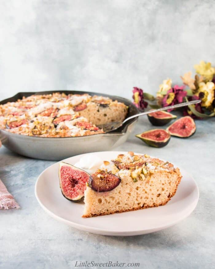 A slice of fig cake on a pale pink plate with the rest of the cake in a skillet in the background.
