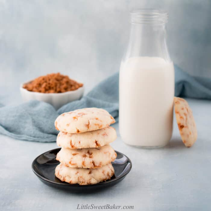 A stack of Skor bit shortbread cookies with one leaning on a tall glass of milk.