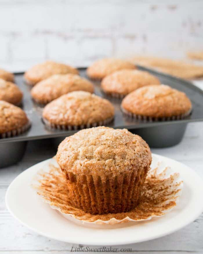 A banana muffin with its paper liner peeled on a white plate.