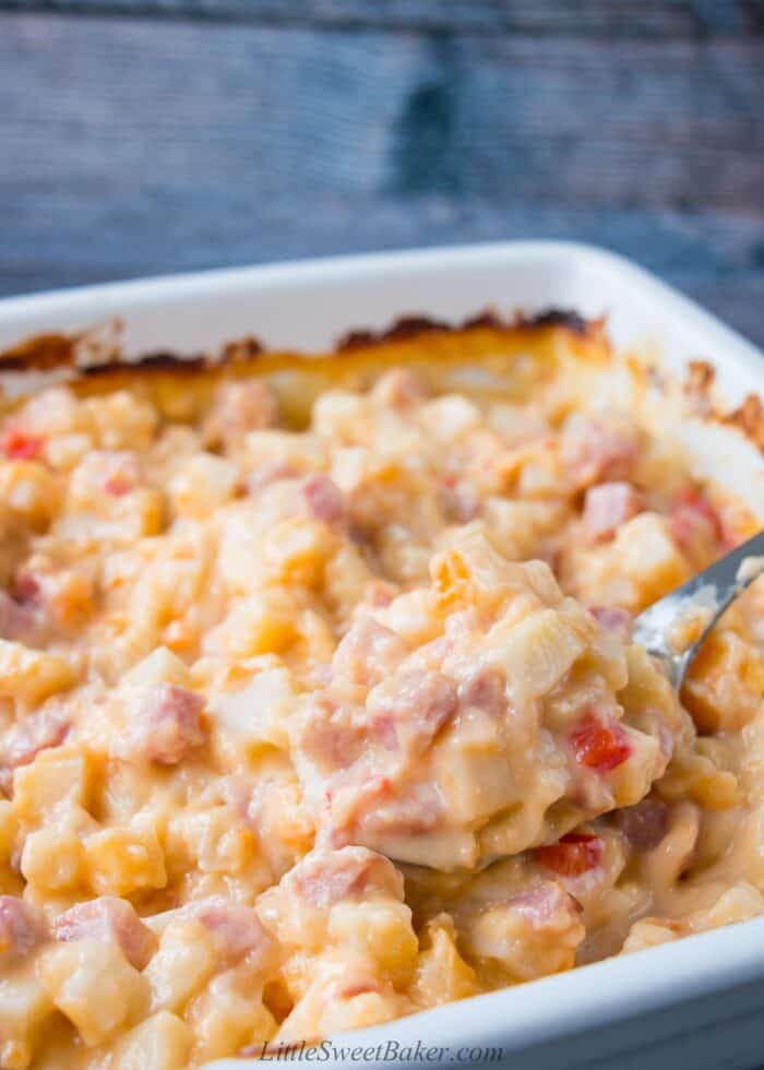 A dish of ham and potato casserole with a spoon being scooped out.