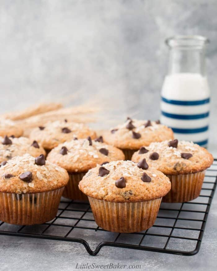 Oatmeal chocolate chip muffins on a cooling rack with a glass of milk behind.