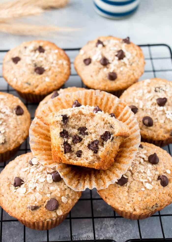 Oatmeal chocolate chip muffins on a cooling rack with a big bite taken out of one.
