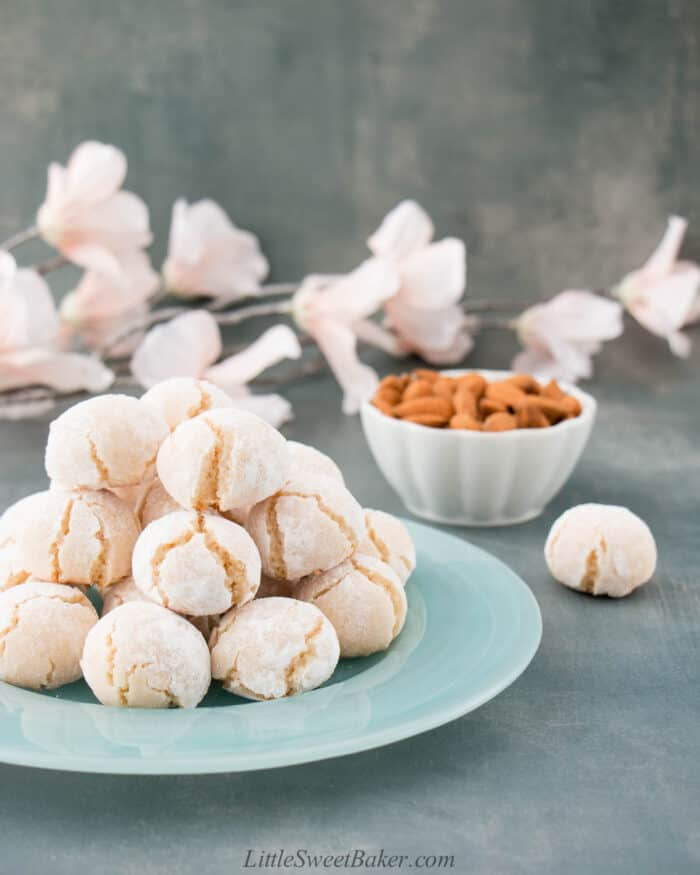 A plate of soft amaretti cookies with a bowl of almond and flowers in the background.