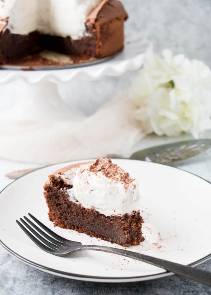 A slice of flourless chocolate torte topped with whipped cream and chocolate shavings.
