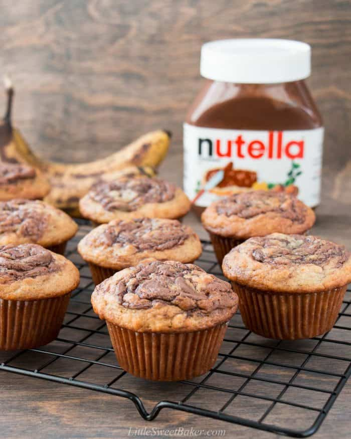 Nutella banana muffins on a cooling rack with a jar of Nutella in the background.