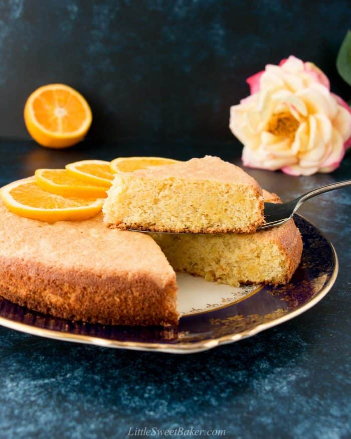An orange almond cake on a vintage plate with a sliced lifted.