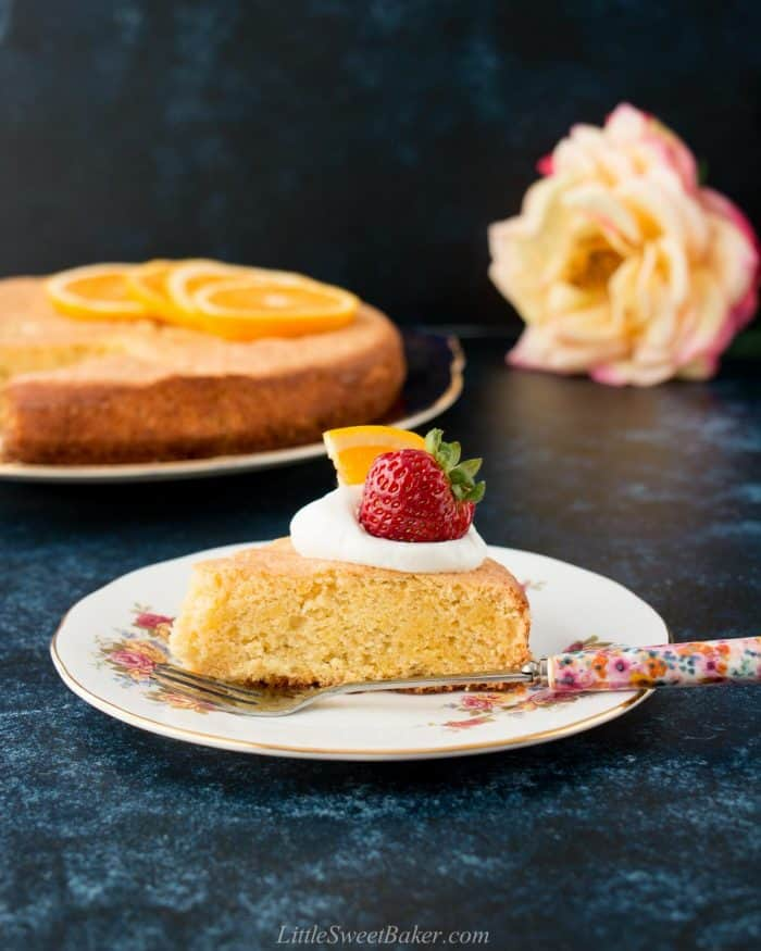 A slice of orange almond cake topped with whipped cream, strawberry and orange slice.