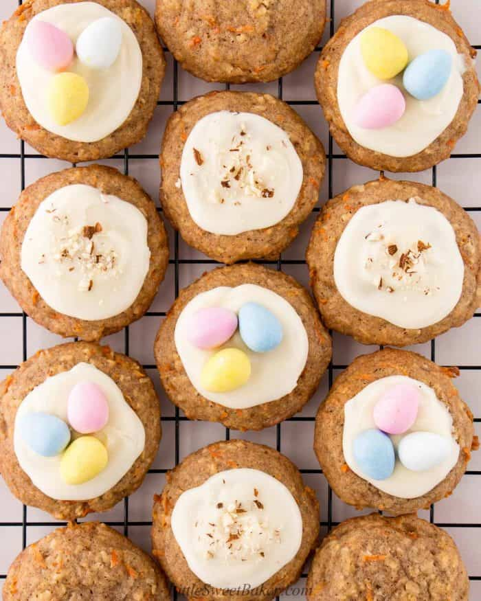 Carrot cake cookies topped with cream cheese, mini eggs and chopped nuts on a cooling rack.