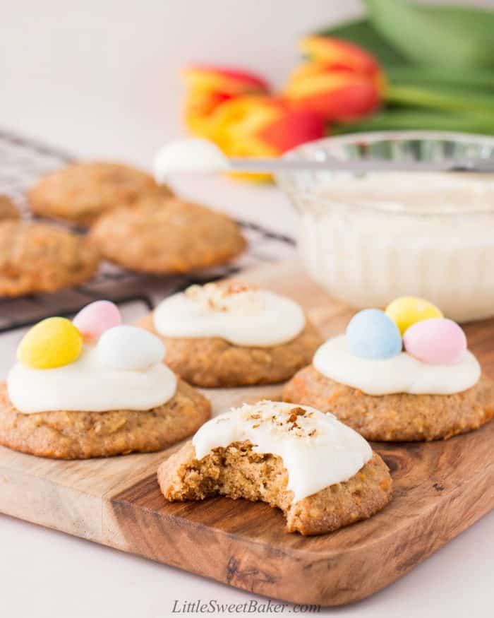 Carrot cake cookies with cream cheese frosting on a wooden board with a bite taken out of the front cookie.