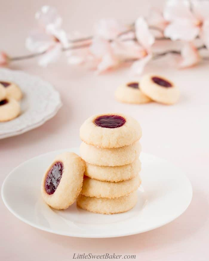 Six raspberry thumbprint cookies on a small white plate.