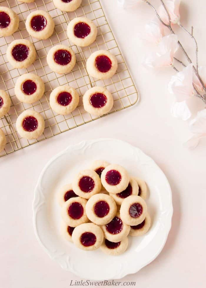 Raspberry thumbprint cookies on a cooling rack and on a white serving plate.