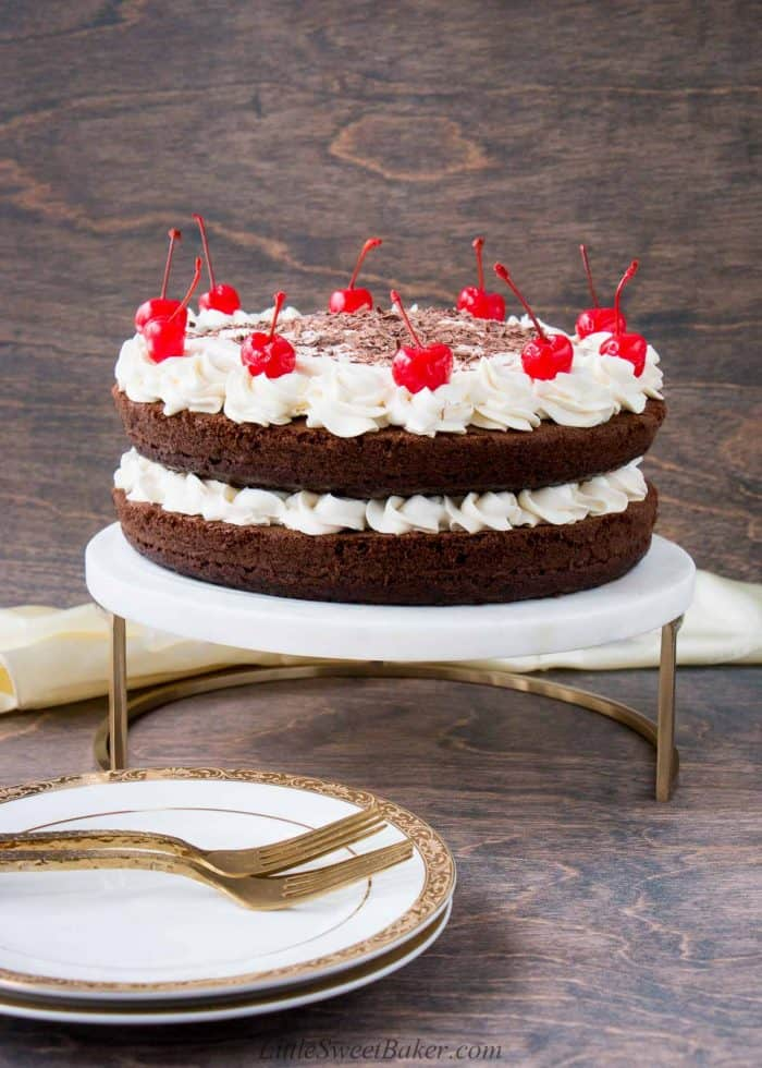 A whole black forest cake on a marble and gold cake stand.