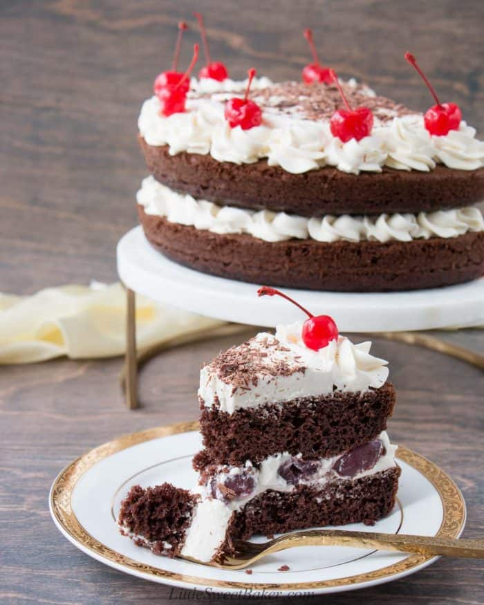 A slice of black forest cake on a white and gold plate.